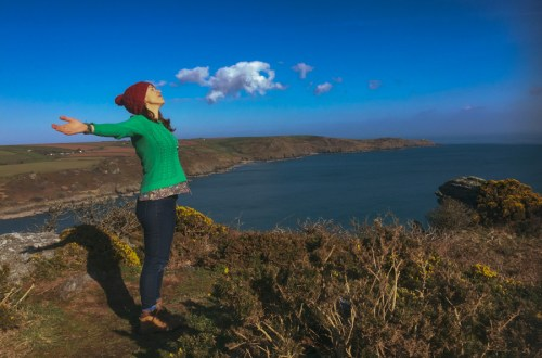 image of a woman in a green jumper and red hat standing on the cliffs with arms spread out wide, smiling