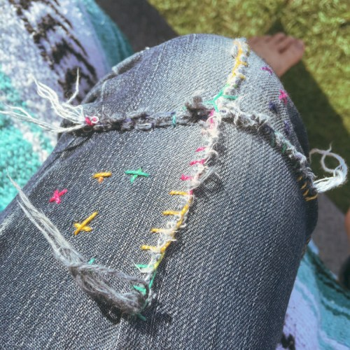 Image of a torn pair of jeans which have been sewn up with colourful thread