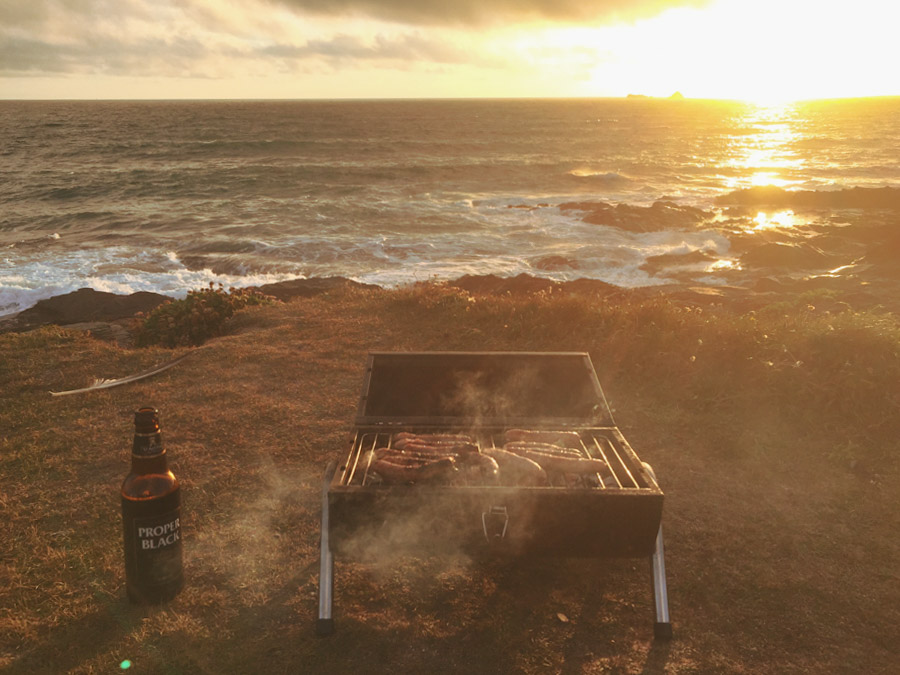 image of sausages cooking on a barbeque beside the sea at sunset