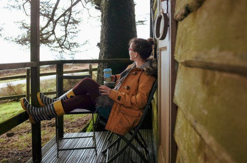 image of a woman sat on a wooden deck outside a cabin with a a cup of coffee
