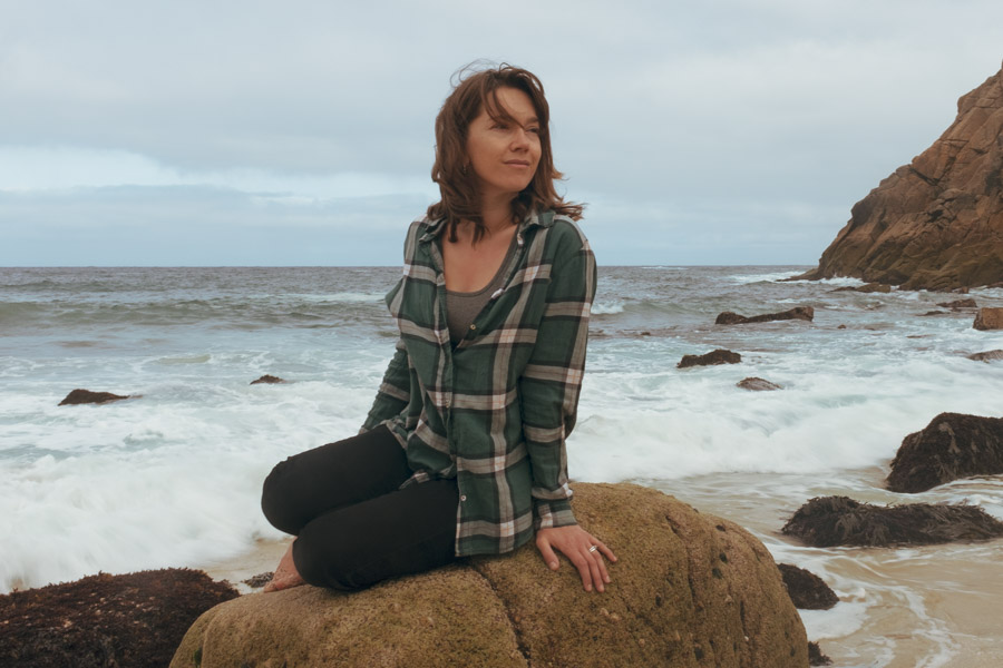 image of a woman sat on a rock by the sea
