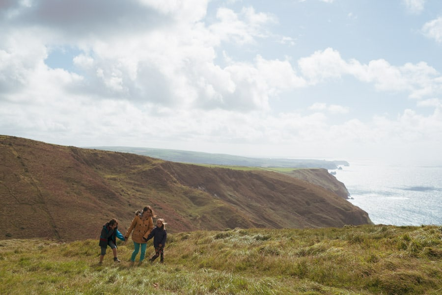 family taking a walk on a coastal path, views of cliffs and ocean