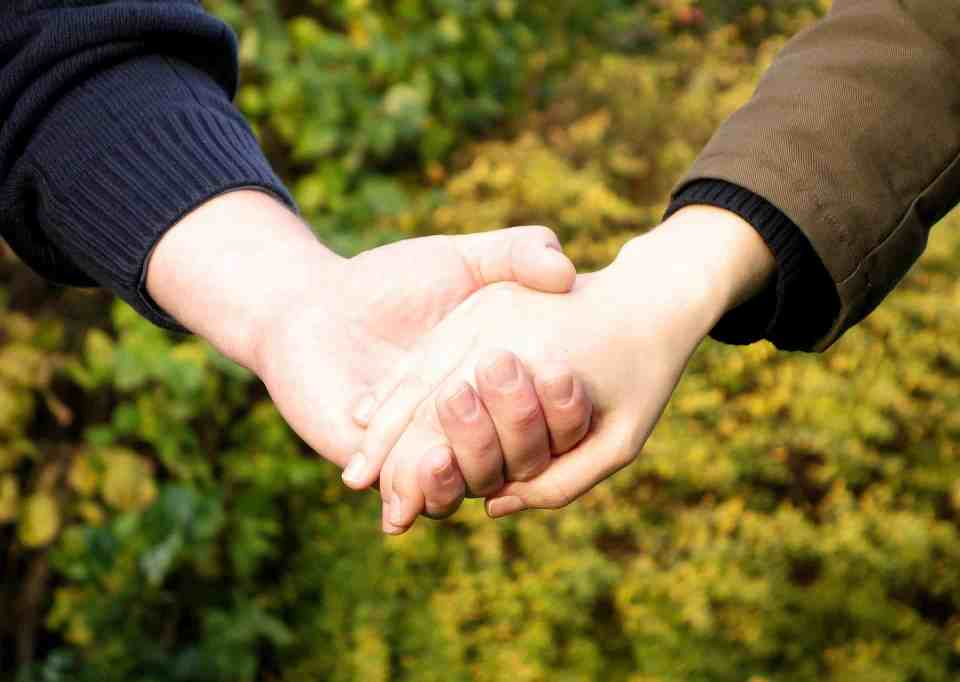 close up image of holding hands