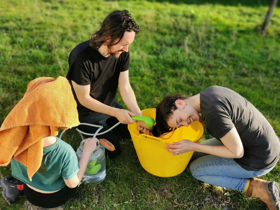 image of a man washing his wife's hair in a trug tub