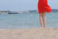 Asian girl with red dress on seashore - in Cannes