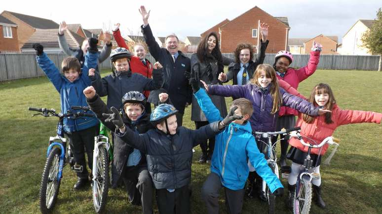 Councillor William Webb, Miss Anna Piperissa and pupils from St. Hugh's Catholic Primary School celebrating news that they have received funding for new cycle storage.