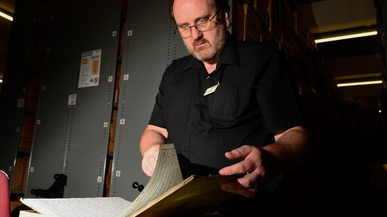 Mike Rogers browses through the old handwritten records at the Lincolnshire Archives in Lincoln. Photo: Steve Smailes for The Lincolnite