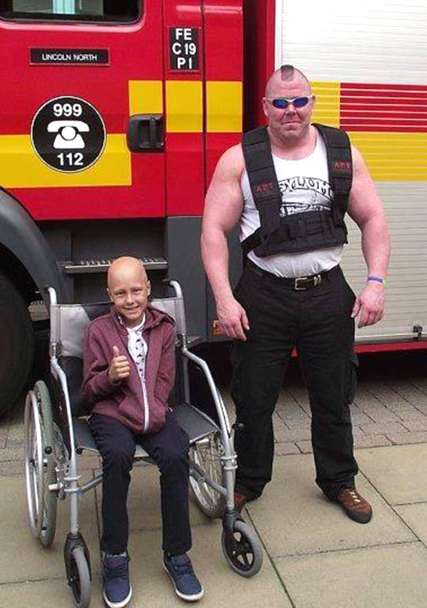 Ethan Maull with charity fundraiser David Johnson at his annual Firetruck Pull.