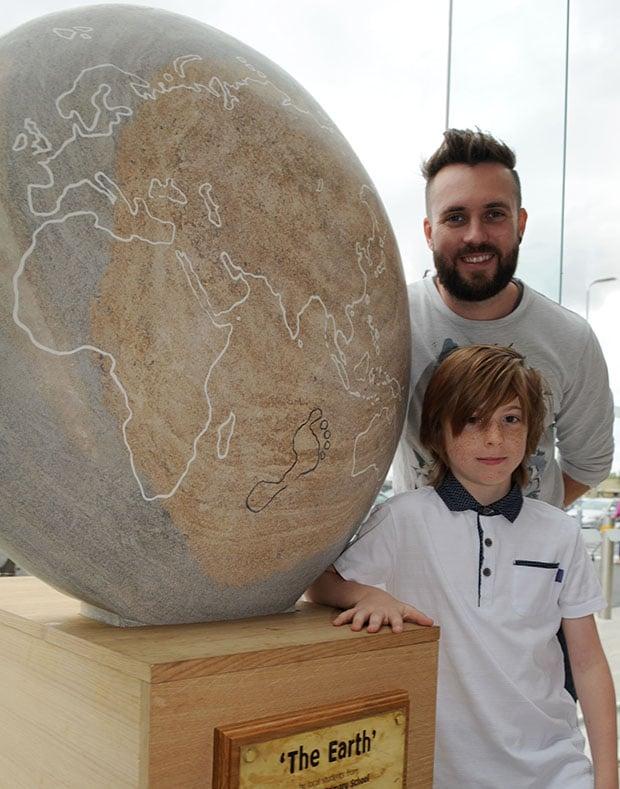 Tyler Goy (9) with sculpter James Sutton.
