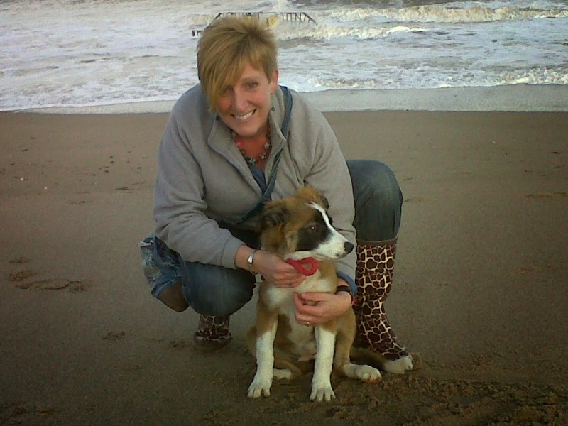 Cute as a button! Maya at the beach with owner Joanne when she was a puppy.