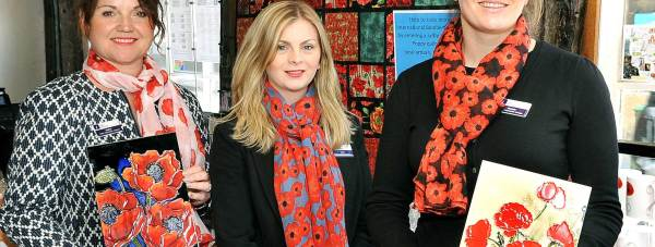 (R-L) Lincoln Visitor Information Centre Manager Michele Sims with colleagues Laura Hall and Rachel Harris-Jones, who are all wearing their Poppy Scarves, and showing some of the souvenirs available for visitors to the poppies sculpture.