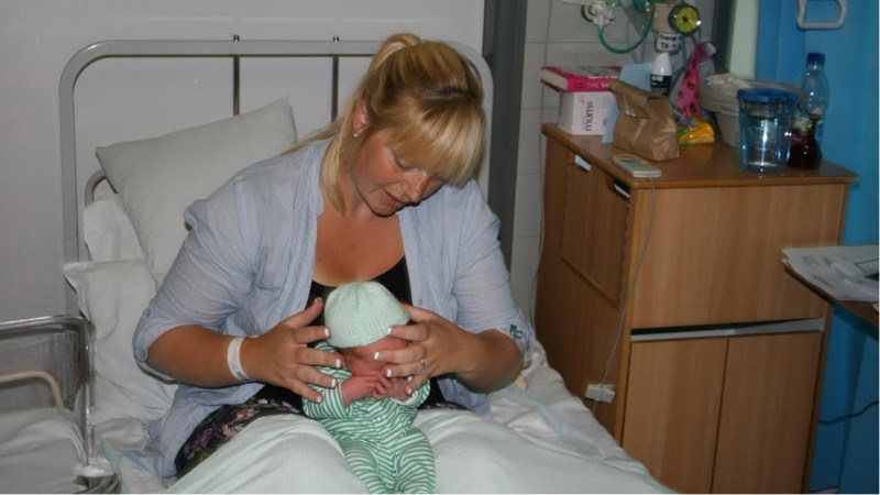 Mother Bonnie Henton puts one of the hats on baby Fergus Henton, aged 2 days.