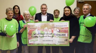 Cheque handover to Christine Lucas, acting Chair of the Branch, by Chris Illsley and Caroline Birkin, Co-Founders and joint CEOs of Running Imp with Faye Watson, Managing Director and some of the Lincoln Branch Samaritans Volunteers