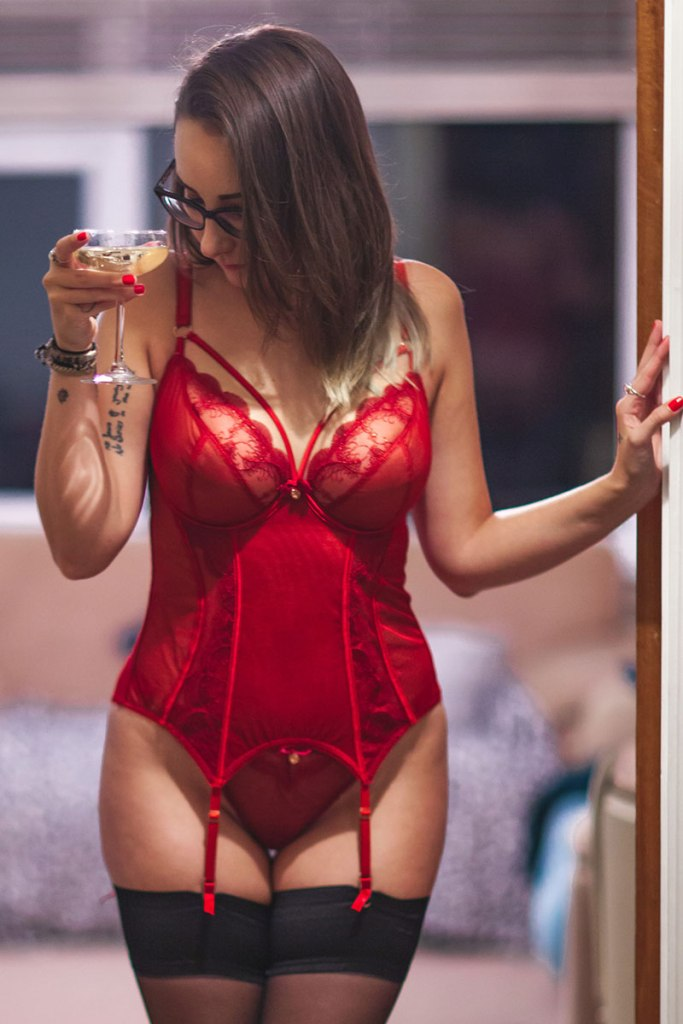 lucy wears the scantilly surrender red basque and thong in 30F and S with a pair of black stockings, holding a martini glass