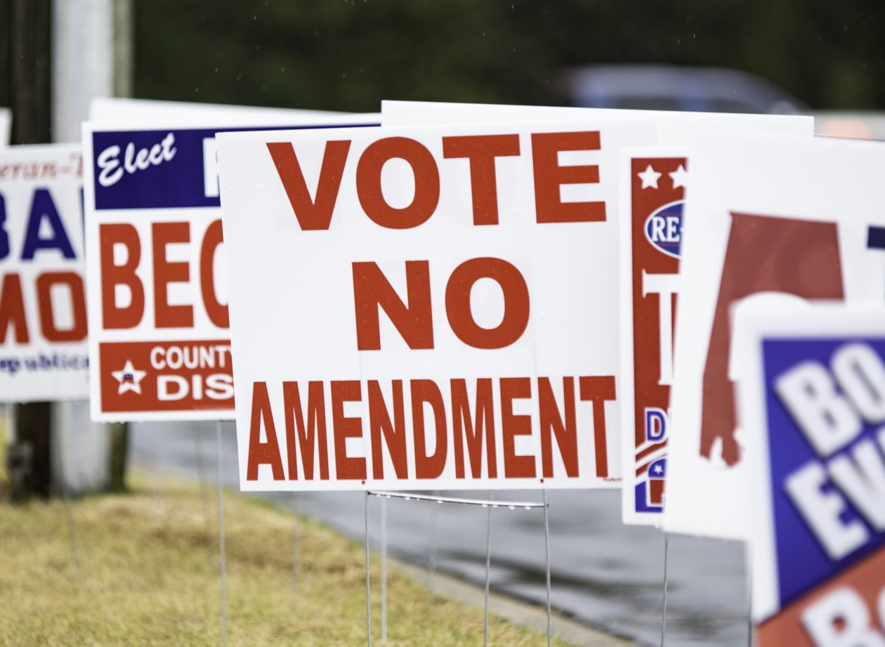 Political sign urging Vote No Amendment within a sea of other annonomous political campaign signs on a rainy day.