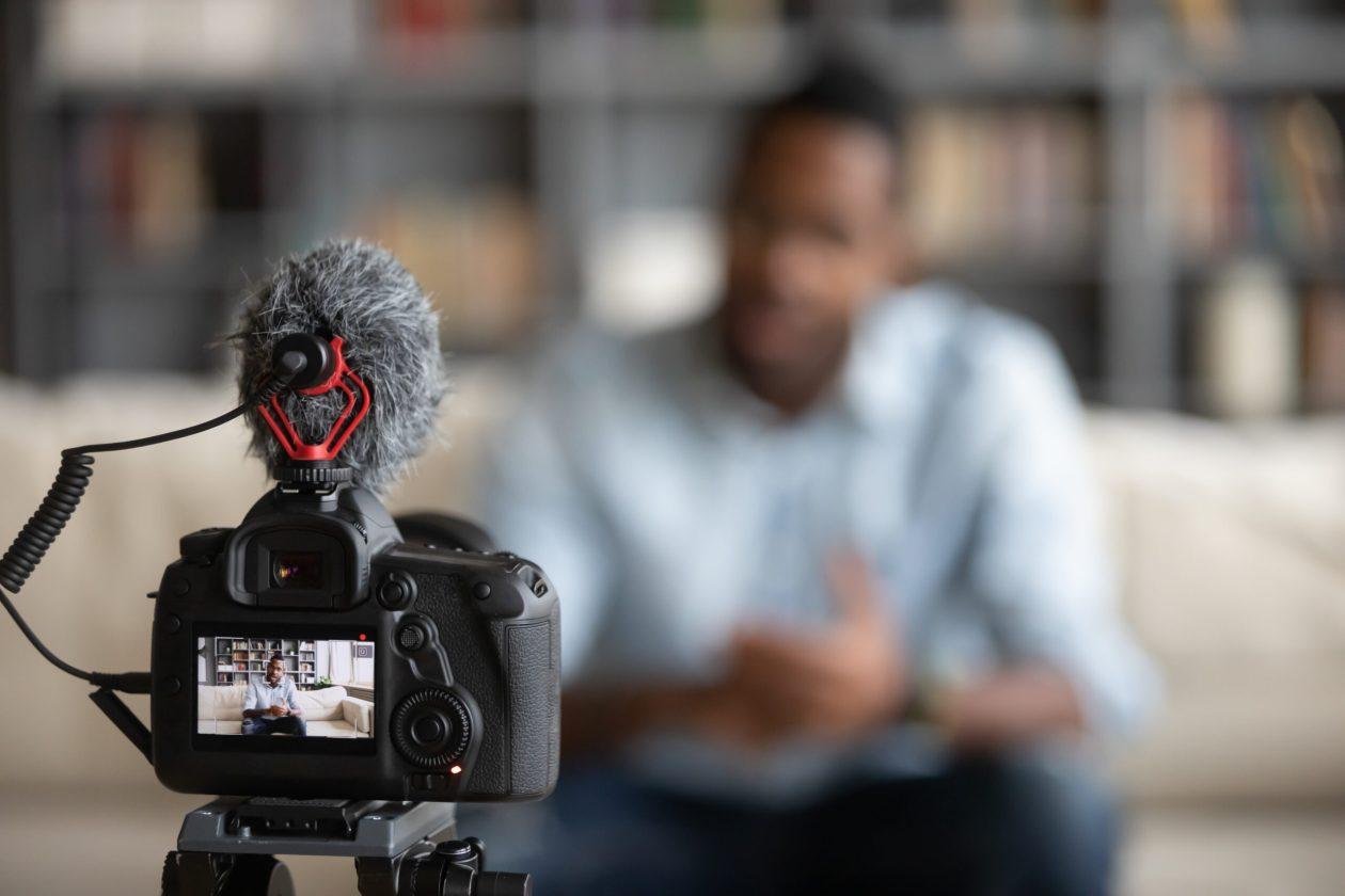 Professional camera shooting biracial blogger making vlog