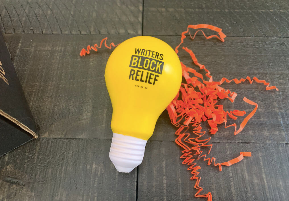 "Lightbulb-Shaped Stress Ball reading ""Writers Block Relief"""