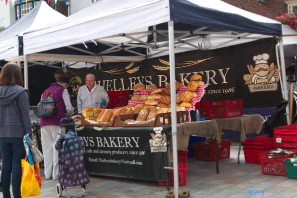 Baker's stall piled high with colourful loaves at Salisbury Market, UK