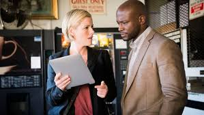 Detectives Kathleen Robertson and Taye Diggs discuss a blank sheet of paper (photo credit TNT)