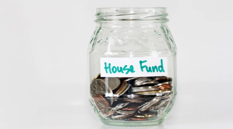"""A jar full of change labeled """"House fund"""""""