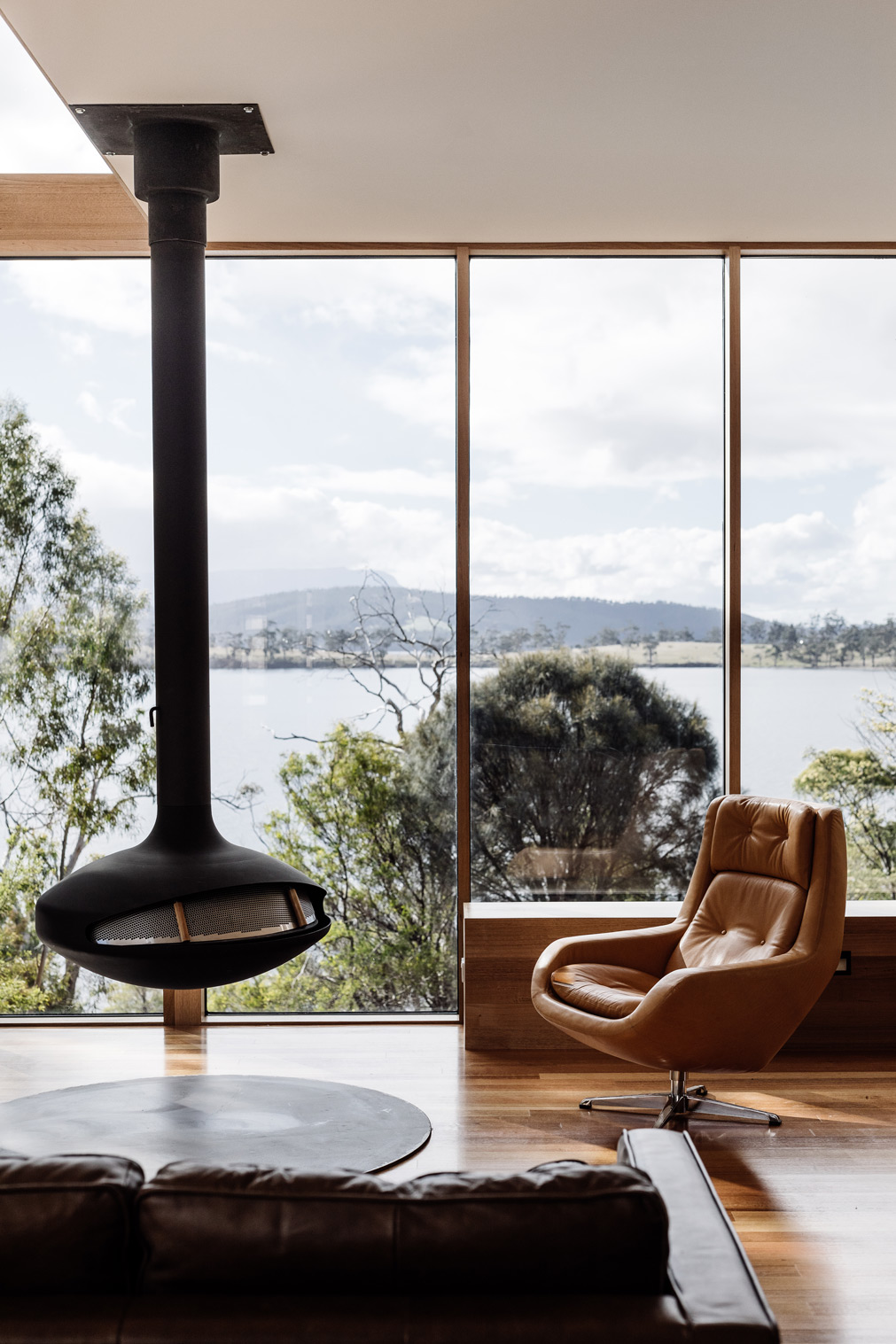 On The Shores Of Bruny Island, An Angular Black Clad Form Emerges From The Coastal Vegetation.
