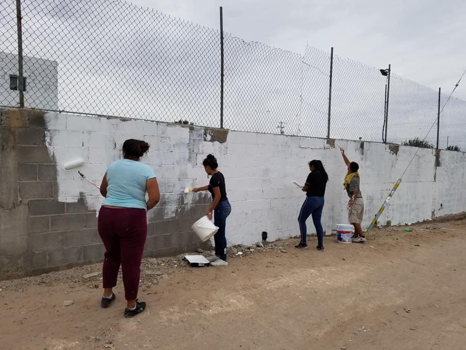 youth painting cinder block walls