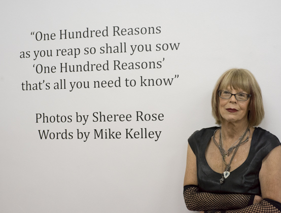 "Photographer and performance artist Sheree Rose at her ""100 Reasons"" photo exhibit opening at Coagula Gallery. Each photo was printed on aluminum and are named by paddle titles taken from Mike Kelly's poem of the same name."
