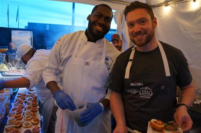 Dan Doherty of  Duck and Waffle and crew prepare pork and N'duja sausage sliders topped with smoked eggplant and yogurt.