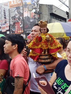 A devotee carrying a statue of Sto. Niño (Child Jesus) at the Solemn Procession.
