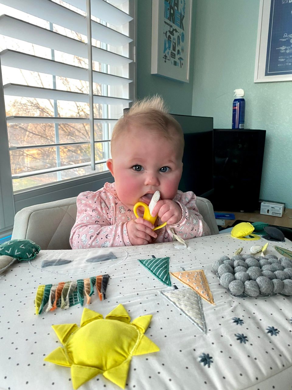 baby in activity chair with teething banana