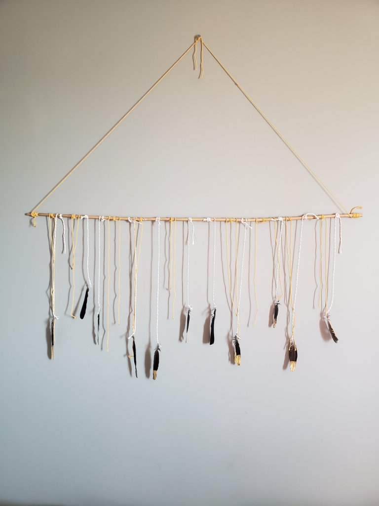 Move over macrame. How to make a feather and wood wall hanging | Luxuriously Thrifty