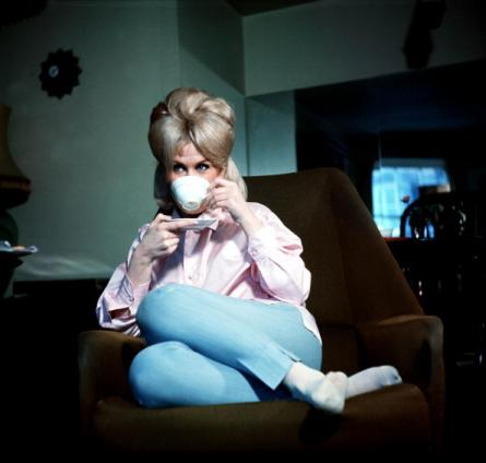 1963. A picture of British singer Dusty Springfield, relaxing on a chair drinking a cup of tea.