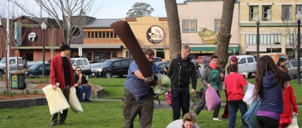 Zac Shank wields his pillow weapon above his head moving toward a fellow pillow fighter. Photo by | Curran Daly