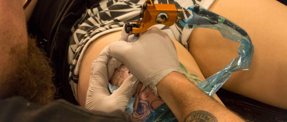 Joe Elliot, from Tattoo Joe's in Vacaville, California working on a client's thigh piece. Photo by Carlos Olloqui.