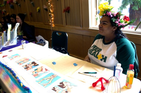 Peer Health Educator giving information about massages and giving away free coconut oil. | Photo by Sarahi Apaez