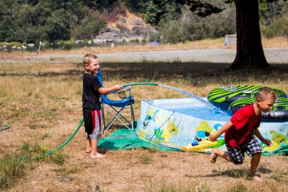 Colin Retz sprays Damian Schoenberner with a water hose at the Mad River.