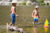 Brothers Darius and Marcellus Mason play in the water with their toy boats at Mad River.