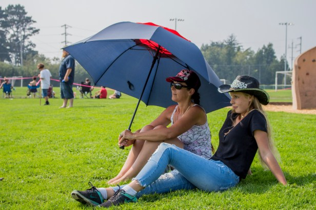 Mother Jessica and daughter Lorriann Ramsey cool off under an umbrella and hat while watching a soccer game at the Arcata Community Center soccer field.