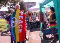 Rainbow flag cape blows in the wind at Humboldt pride. | Kyra Skylark
