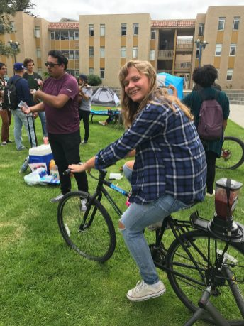 Student at Outdoor expo riding the smoothie bike to operate the bicycle powered blender. Photo by Jessenya Guerra.