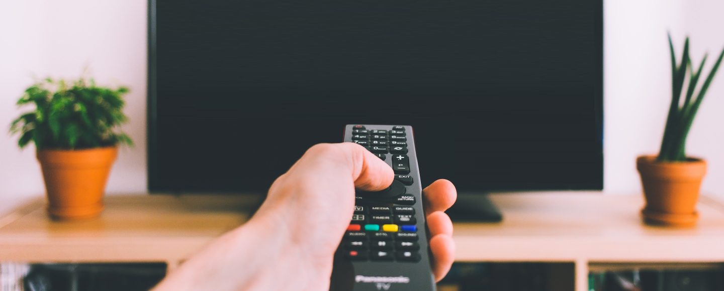 A hand holds a remote control in front of a television.