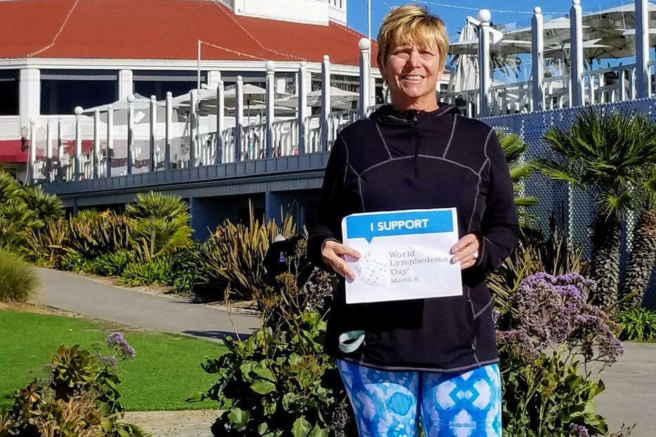 Harmer holds a sign in support of World Lymphedema Day.