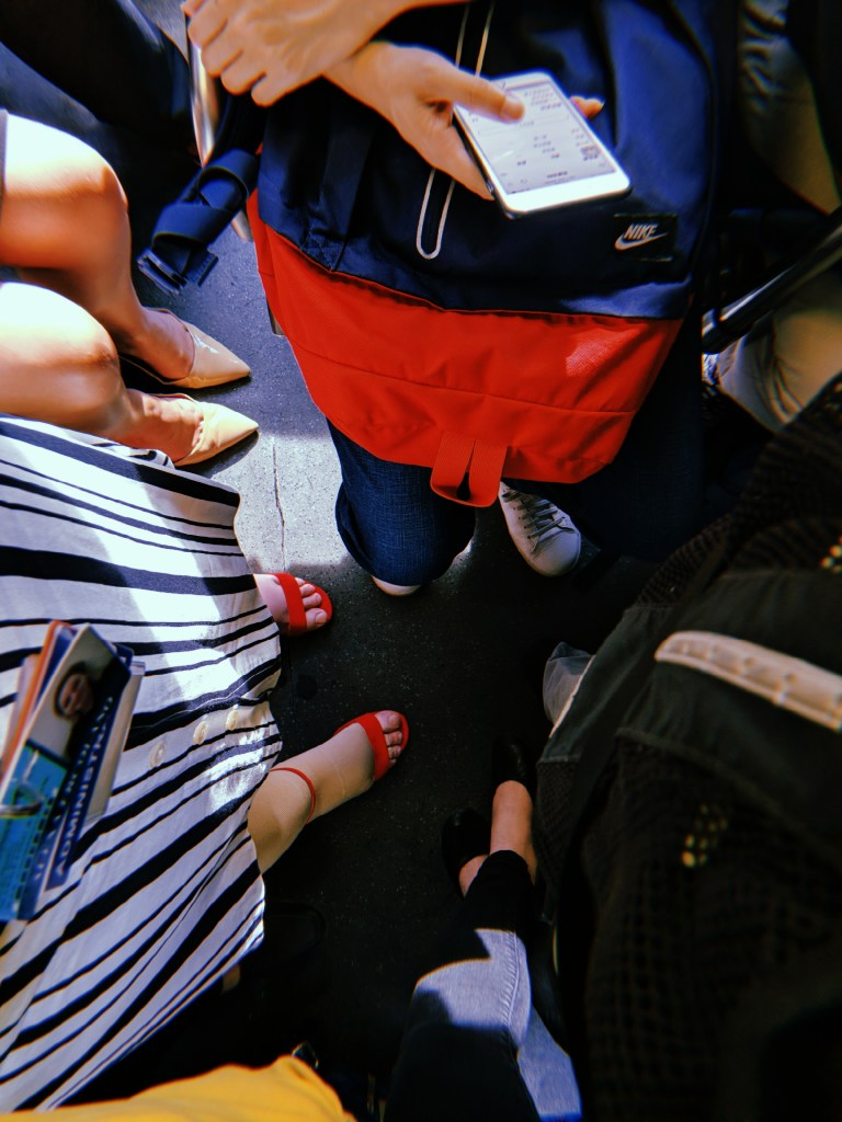 Looking down at the bus floor, we see Alexa's feet in red heels along with the feet of other passengers.