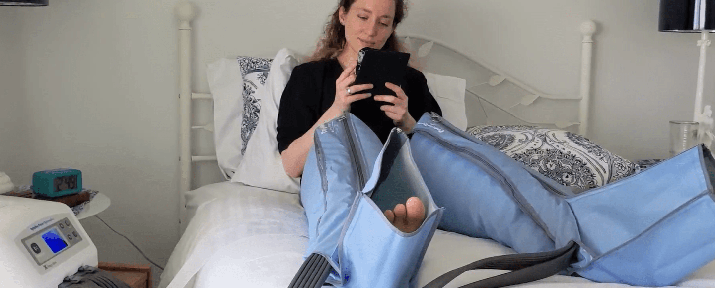 Alexa sits on a bed, her legs in compression sleeves, while undergoing a compression pump treatment. She is reading a Kindle, smiling slightly.