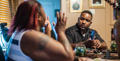 Tory Lowe, 39, a prominent activist in Milwaukee, visits with Carolyn Williams, 44, whose son was shot by police under questionable circumstances. Photo by André Chung.