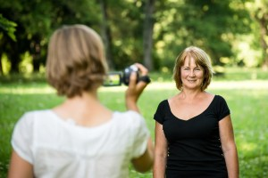 Woman is taking video of her senior mother in nature with camcorder