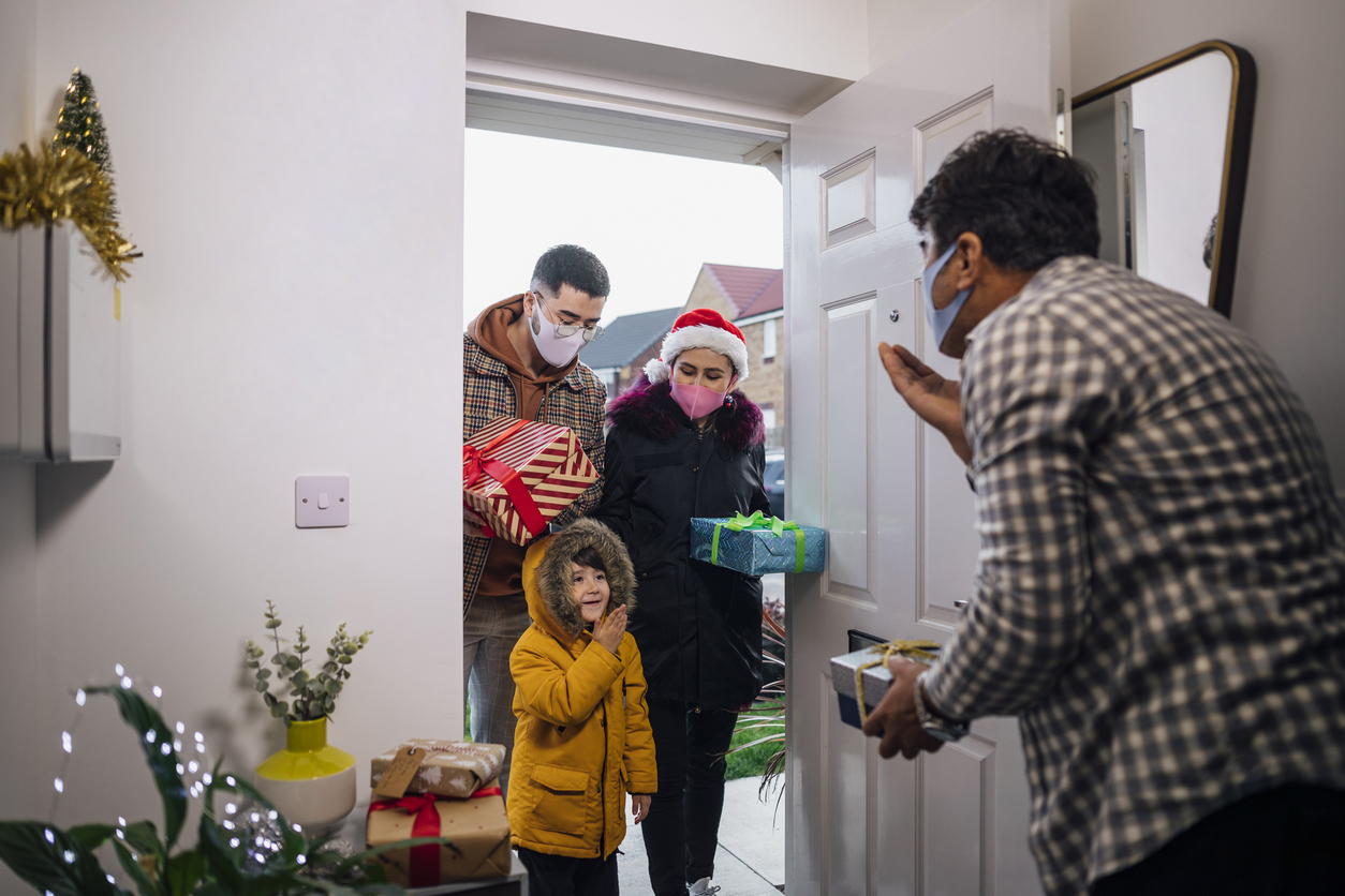 A senior man welcoming his holiday guests into his newly decorated and clean home.