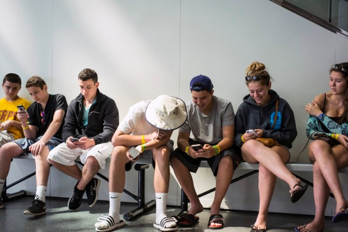 Teens Look At Their iPhones At The Rock And Roll Hall Of Fame