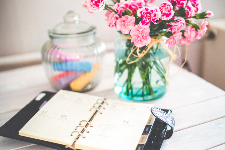 Flowers sitting on desk with open planner