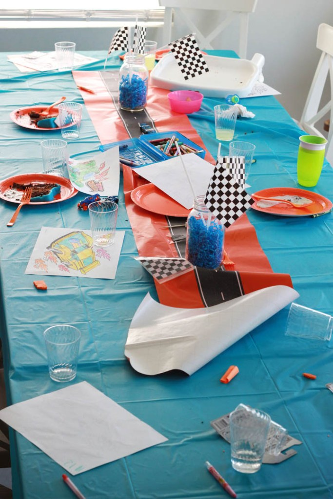 Aftermath of Hot wheels birthday party. Messy table with empty plates and used coloring pages.